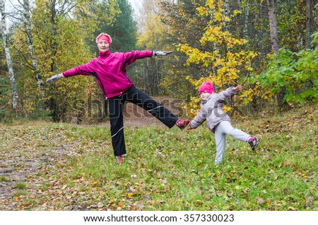 Woman with girl doing aerobics in the park - stock photo