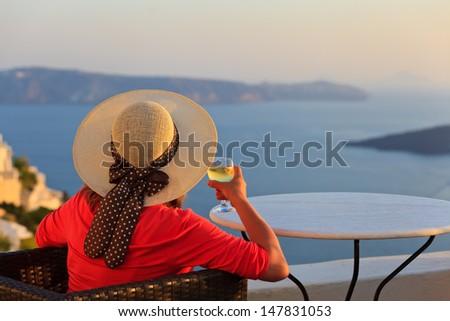 woman with glass of wine enjoying sunset at Santorini, Greece - stock photo
