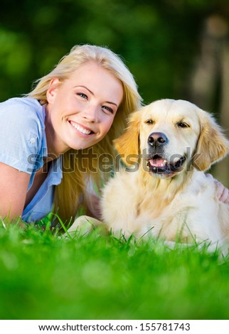 Woman with golden retriever lying on the green grass in the park, close up - stock photo