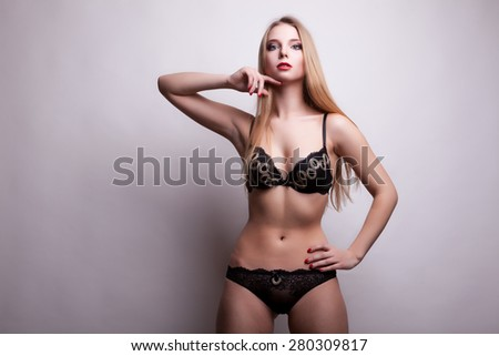 Woman with gorgeous body in underwear on grey background. Studio shooting. Sexuality and sensuality. Girl in underwear with perfect toned body - stock photo