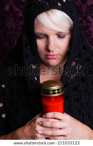 Woman with grave candle - stock photo