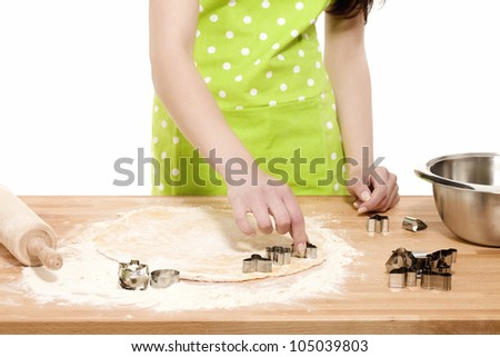 woman with green apron  pressing christmas molds in dough - stock photo