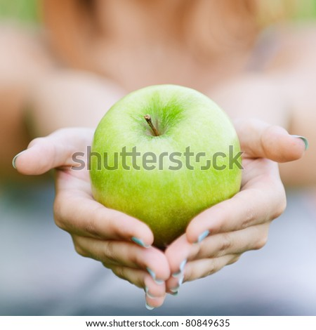 Woman with green big apple, against green summer garden. - stock photo