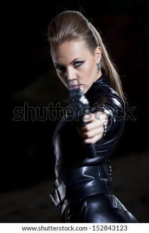 woman with gun in leather suit over black aiming at the camera - stock photo