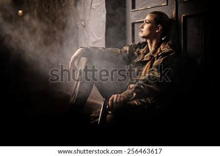 Woman with gun in military uniform - stock photo