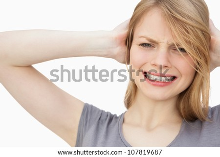 Woman with hand behind her head against a white background - stock photo