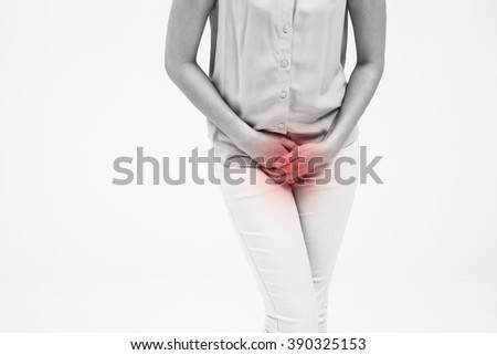 woman with hands holding her crotch isolated in a white background - stock photo