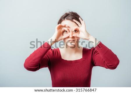 woman with hands makes binoculars - stock photo