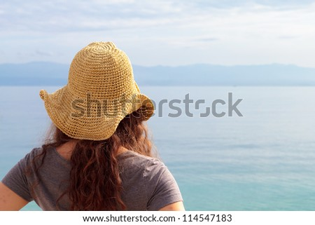 Woman with hat by the sea - stock photo