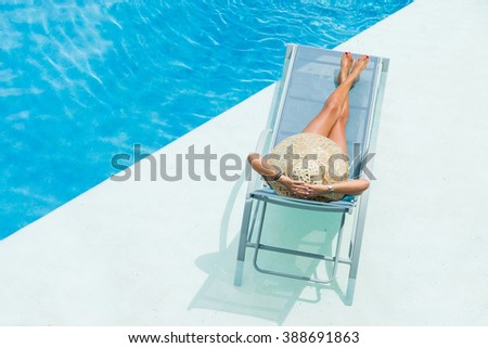 woman with hat  enjoying on sunbed at swimming pool - stock photo