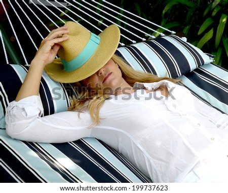 Woman with hat is lying on a hammock/Resting Woman/Woman with a hat is lying on a hammock on a summer day - stock photo