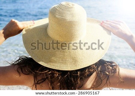Woman  with hat on the beach in summer - stock photo