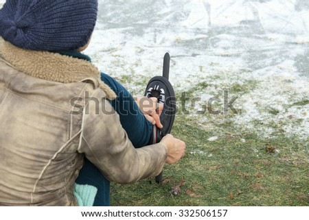 Woman with hat putting on ice skates on the grass - stock photo