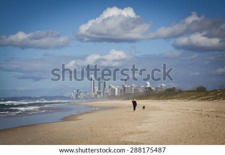Woman with hat walks a dog along a windswept beach on This Spit on the Gold Coast in Queensland, Australia. It is a sand bar off the coast of Southport. Skyscrapers in distance, All logos removed. - stock photo