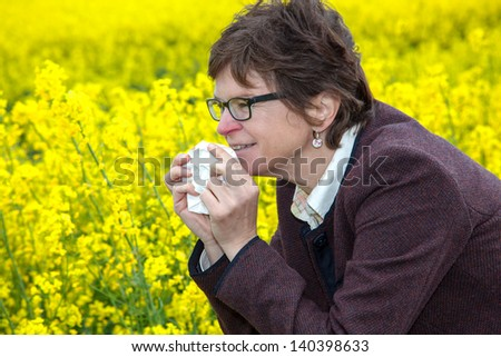 Woman with hay fever on blooming rapeseed field - stock photo
