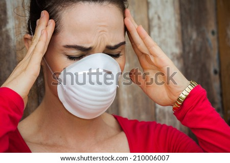 Woman with headache wearing a face mask - stock photo