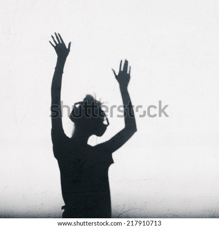 Woman with headphones lifting her hands up. Photo of shadows of dj girl - stock photo