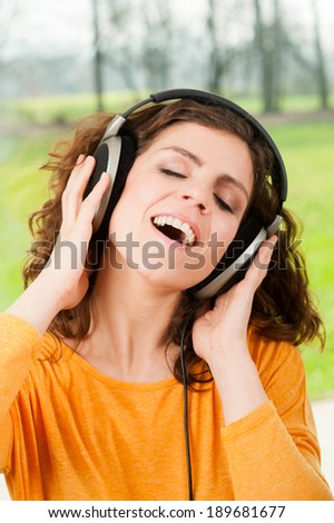 Woman with headphones listening music .Music teenager girl dancing with nature in the background  - stock photo