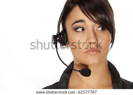 Woman with headset looking to her left, with a worried expression. - stock photo