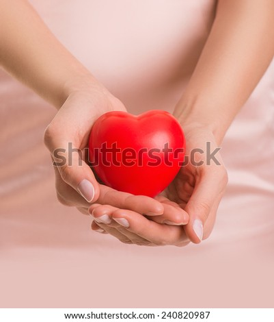 Woman with heart in hands, give love, valentine's day, closeup - stock photo