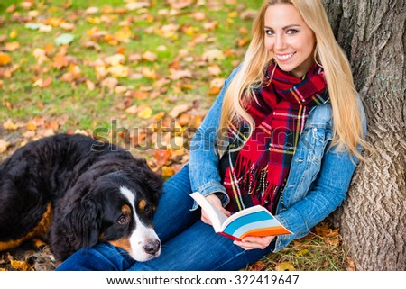 Woman with her Bernese mountain dog reading book in autumn park sitting on meadow covered with foliage - stock photo