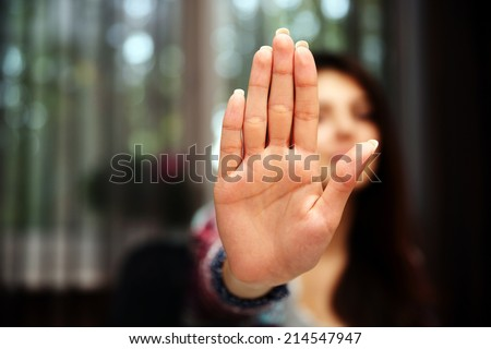 Woman with her hand extended signaling to stop (only her hand is in focus) - stock photo