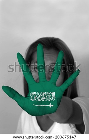 woman with her hands signaling to stop and Saudi Arabia flag - stock photo