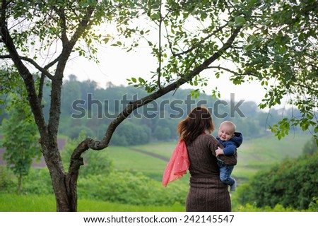 Woman with her little baby walking at the summer park  - stock photo