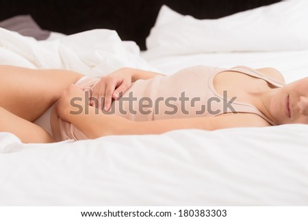 Woman with her monthly menstrual pains clutching her stomach with her hands as she becomes stressed by the ongoing cramps while sitting in her bed - stock photo