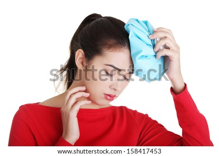 Woman with ice bag for headaches and migraines , isolated on white - stock photo