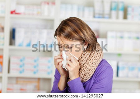 Woman with influenza in the pharmacy blowing her nose on a handkerchief and wearing a thick winter scarf - stock photo