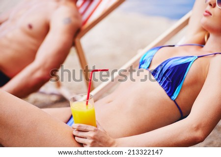 Woman with juice resting in deck chair with man on background   - stock photo