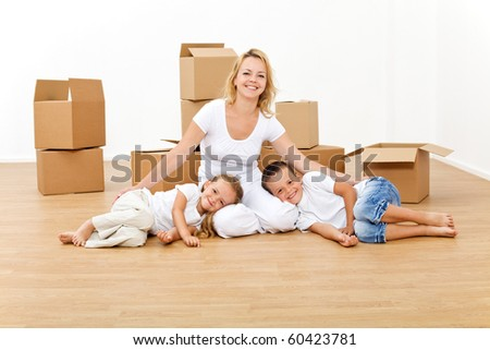 Woman with kids in their new home relaxing on the floor - stock photo