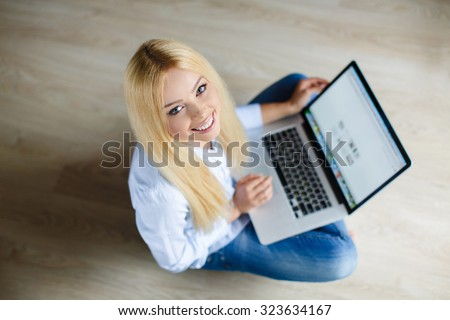 Woman with laptop at home. Top view. Young woman with laptop on the floor. Woman websurfing on the net with laptop. happy young beautiful woman with laptop - indoors - stock photo