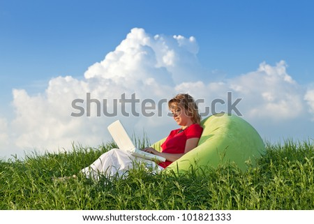 Woman with laptop computer outdoors in the fresh spring grass - stock photo