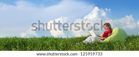 Woman with laptop computer outdoors in the fresh spring grass - panorama - stock photo