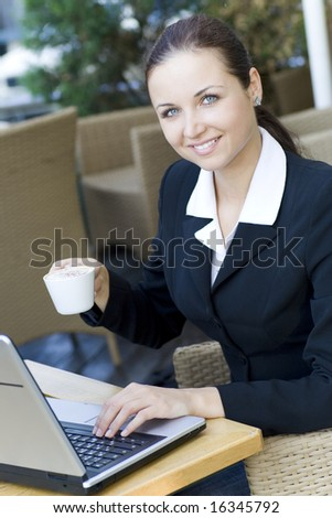 Woman with laptop drinking coffee - stock photo