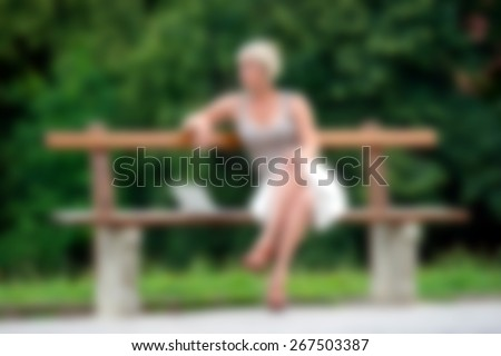 woman with laptop sitting on the bench in the park, blurred for presentation effect, abstract background - stock photo