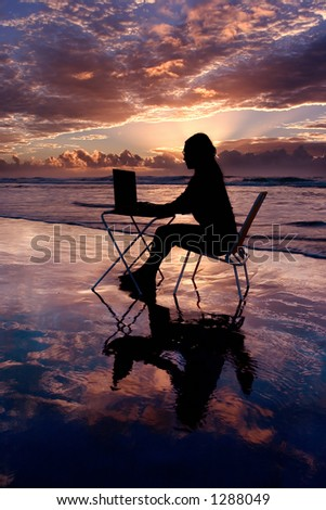 Woman with laptop working at sunrise - stock photo
