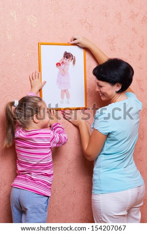 Woman with little girl hanging up a picture - stock photo