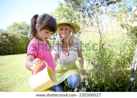 Woman with little girl watering plants in garden - stock photo