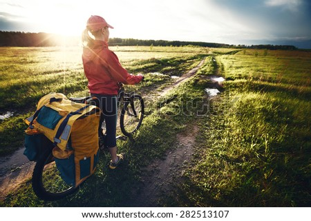 Woman with loaded bicycle on the wet unpaved rural road at sunset - stock photo