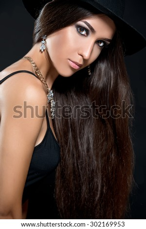 Woman with long beautiful hair and smoky eyes in a hat.  - stock photo