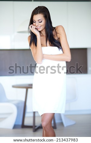 Woman with Long Dark Hair Wearing Bath Towel with Hand Touching Chin and Looking Down - stock photo
