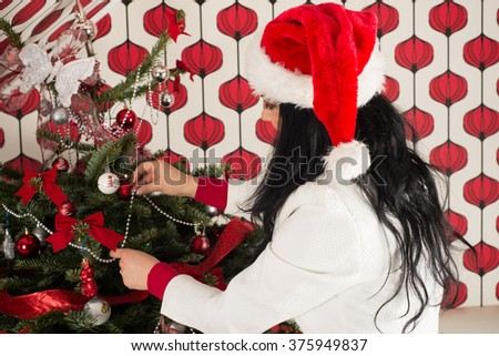 Woman with long hair and santa hat decorate natural Christmas tree - stock photo