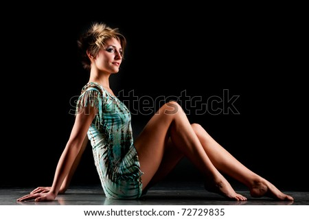woman with long legs and creative hairdo on black background - stock photo