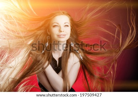 Woman with long luxury hair. Beautiful young stylish fashionable girl with flying hair in the wind - stock photo
