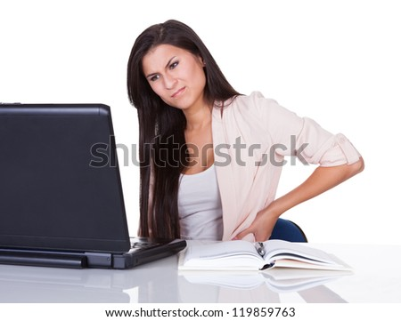 Woman with lower back pain from sitting at her desk in front of her laptop massaging her back with her hand and grimacing - stock photo