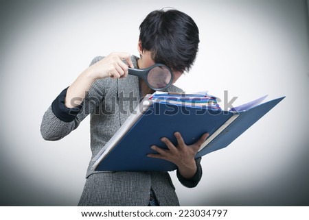 Woman with magnifying Glass Looking at Files / Investigation concept / Checking Law Case Concept / Detective Concept - stock photo