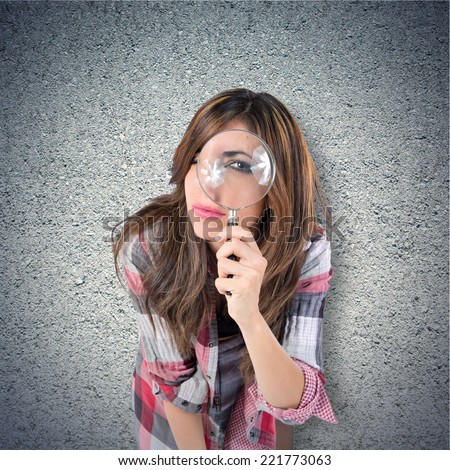 Woman with magnifying glass over textured background - stock photo